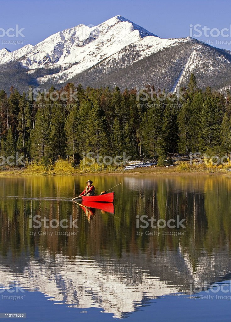 Man Canoeing and Fly Fishing On Colorado Lake stock photo