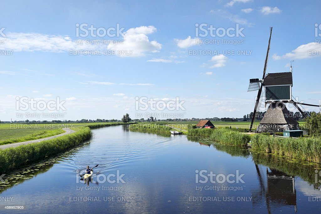 Man Canoeing on a canal in the Alblasserwaard. stock photo