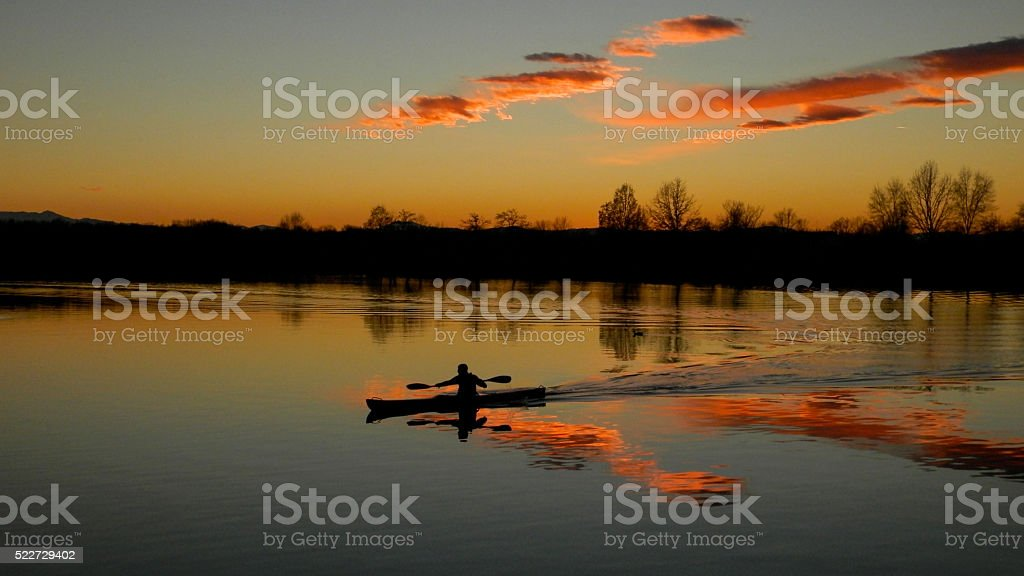Man Canoeing on a Lake: Reflection and Silhouette in Sunset. stock photo