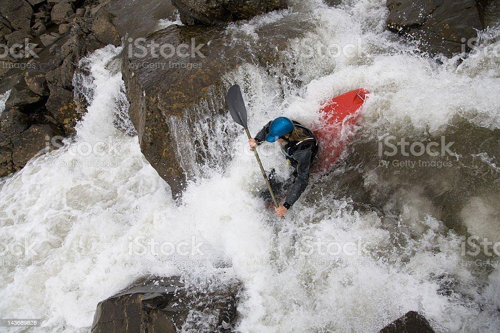 Man canoeing over rocky waterfall stock photo
