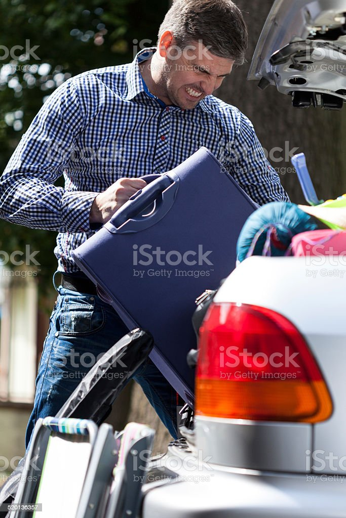 Man can't put luggage into trunk stock photo