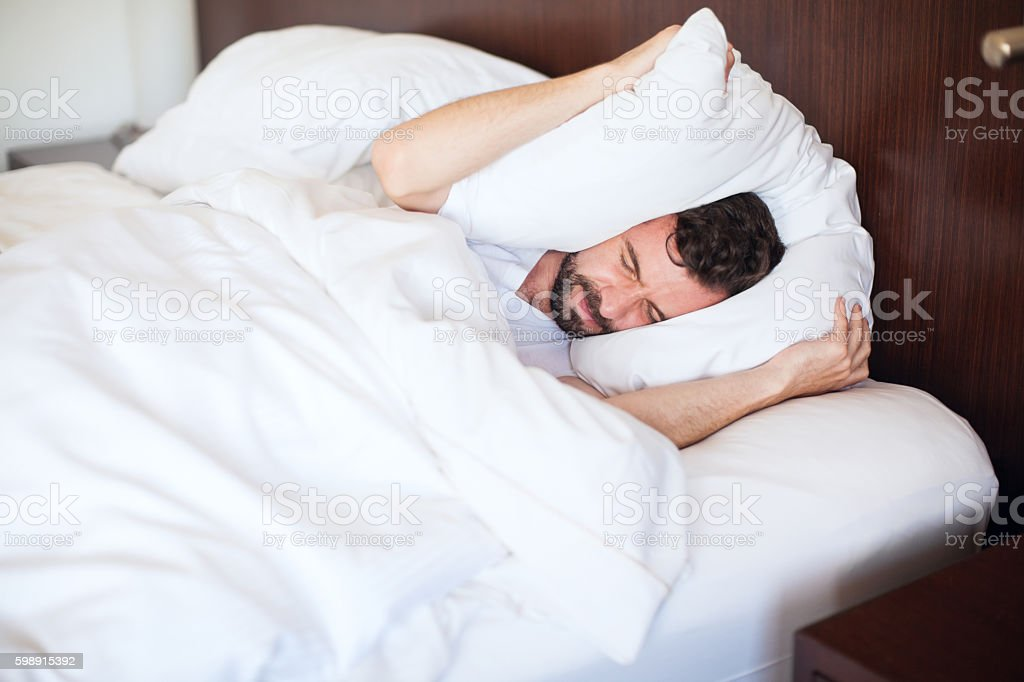 Man can't sleep due to the noise stock photo