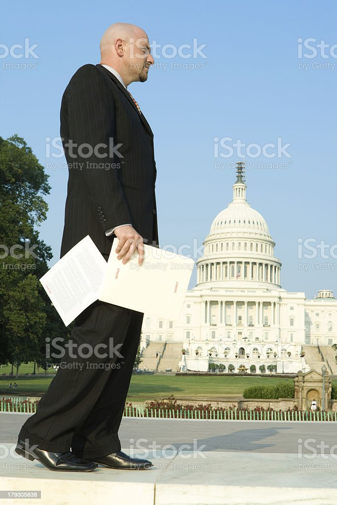 Man Carelessly Dropping Secret Papers Near U.S. Capitol Building royalty-free stock photo