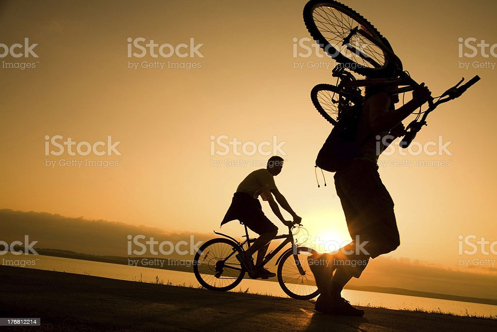 man carries a bicycle at sunset royalty-free stock photo