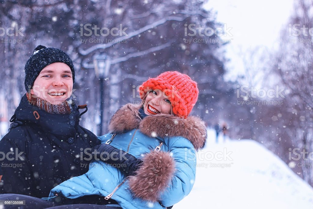 man carries a girl young couple in winter stock photo