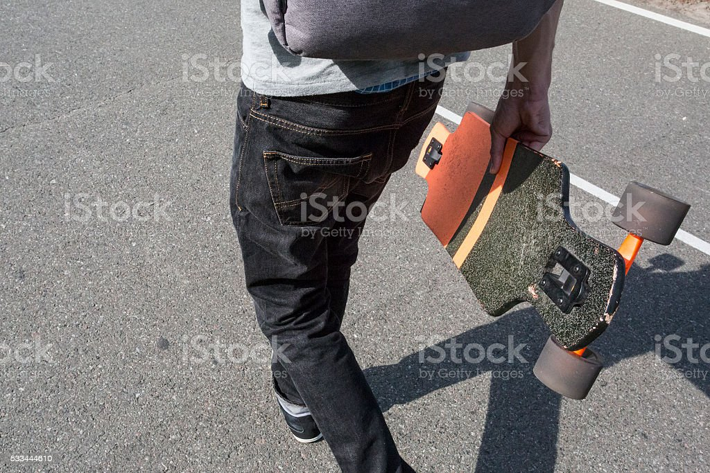 man carries a longboard stock photo
