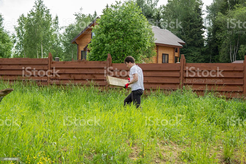 man carries a wooden board in grass stock photo