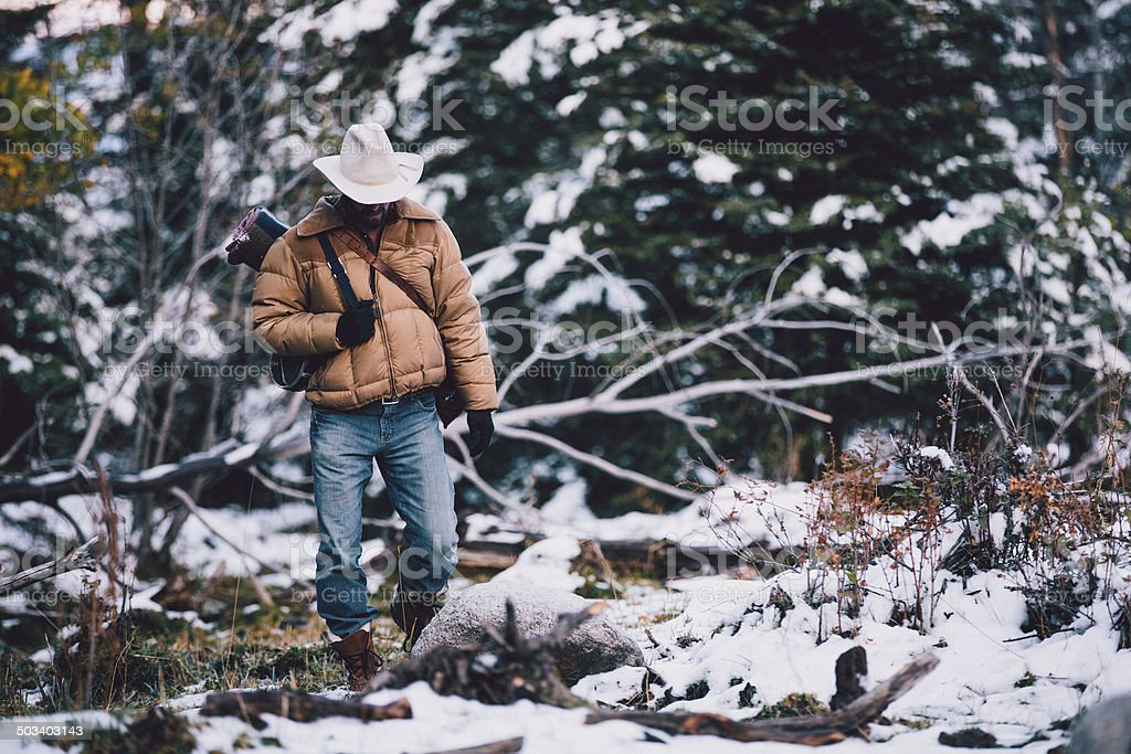Man carries camping gear while walking through snowy woods royalty-free stock photo