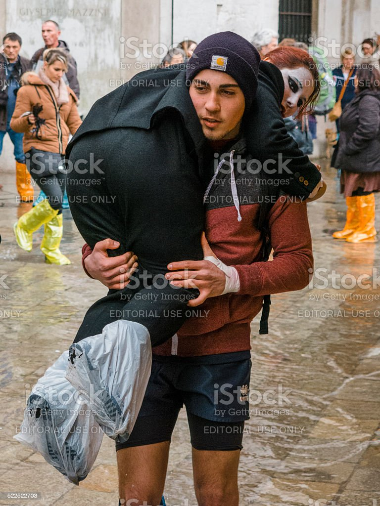 Man carries carnival girl through the flooded waters of Venice stock photo