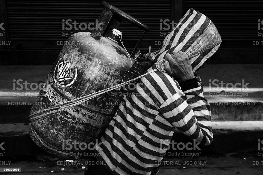 Man carries gas tank stock photo