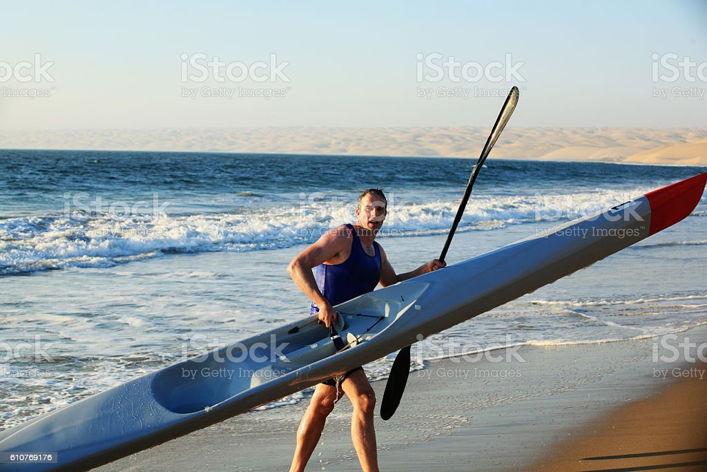 Man carries sea kayak onto the beach from the ocean stock photo