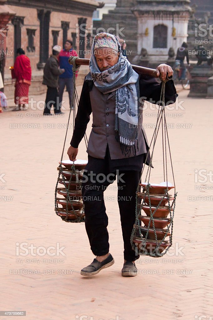 Man carrying a load using a yoke in Bhaktapur, Nepal. stock photo
