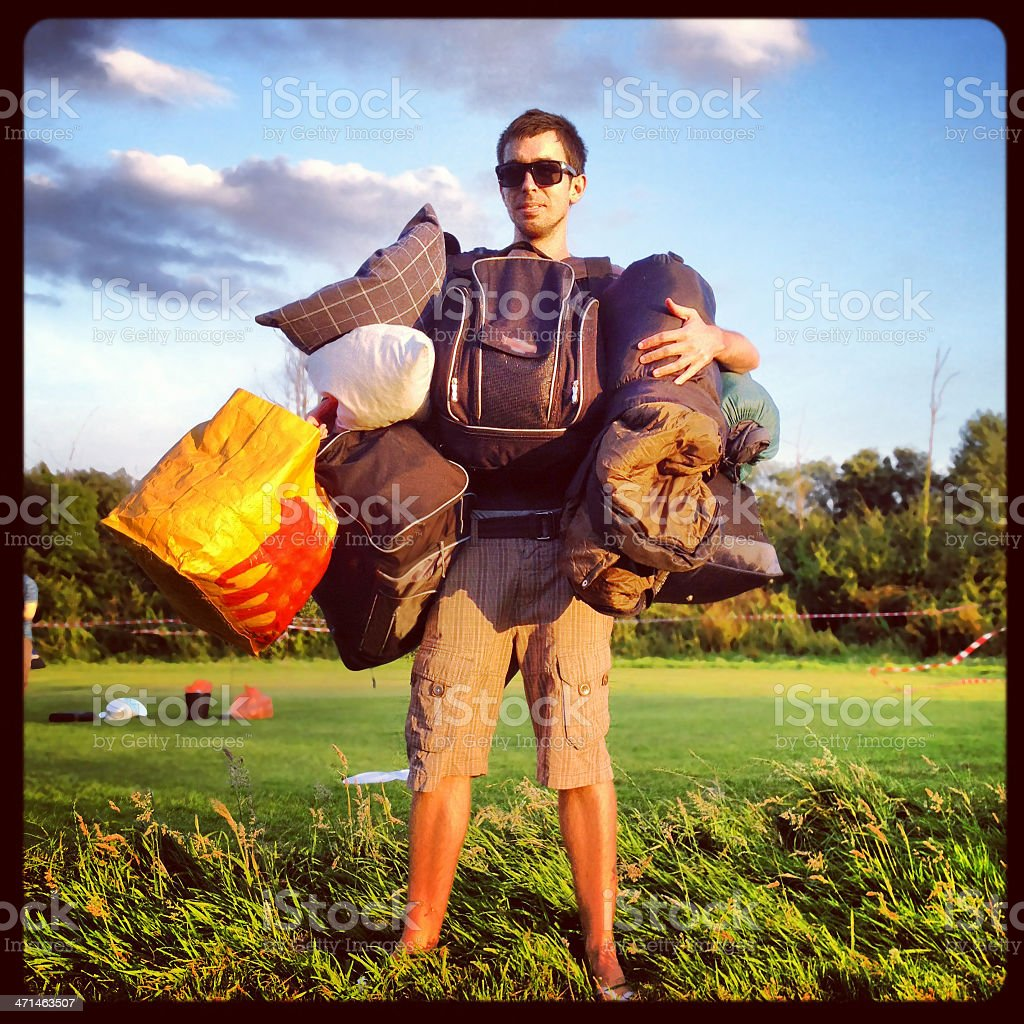 Man carrying a lot of bags for camping stock photo