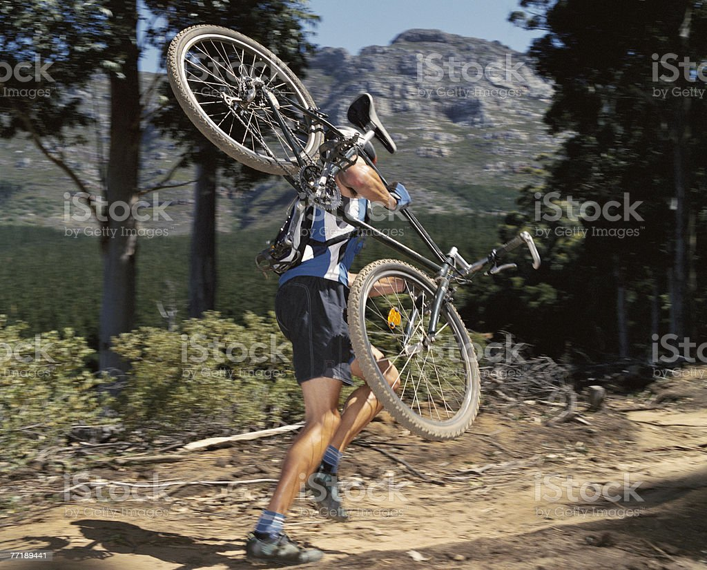 A man carrying a mountain bike on a path royalty-free stock photo