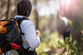 Man carrying backpack standing at forest