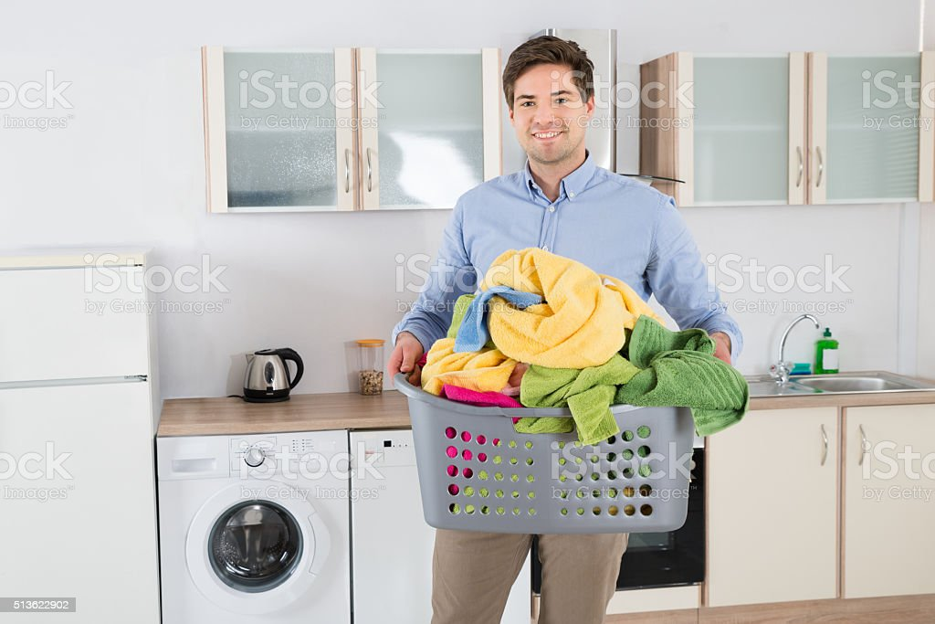 Man Carrying Basket With Heap Of Clothes stock photo