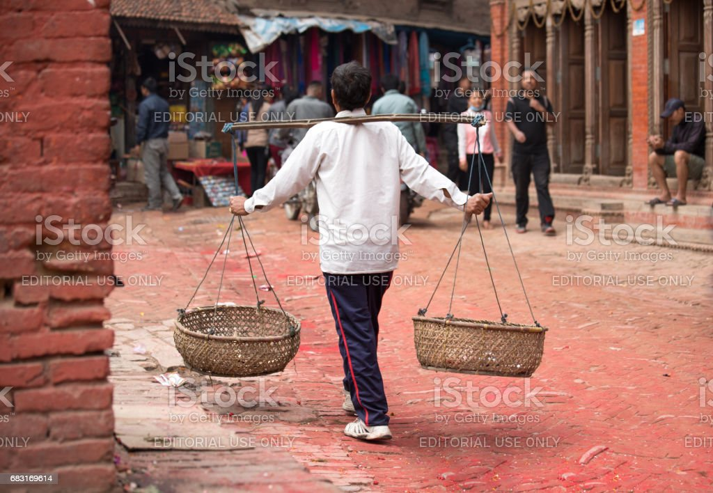 Man carrying baskets on his shoulders. stock photo