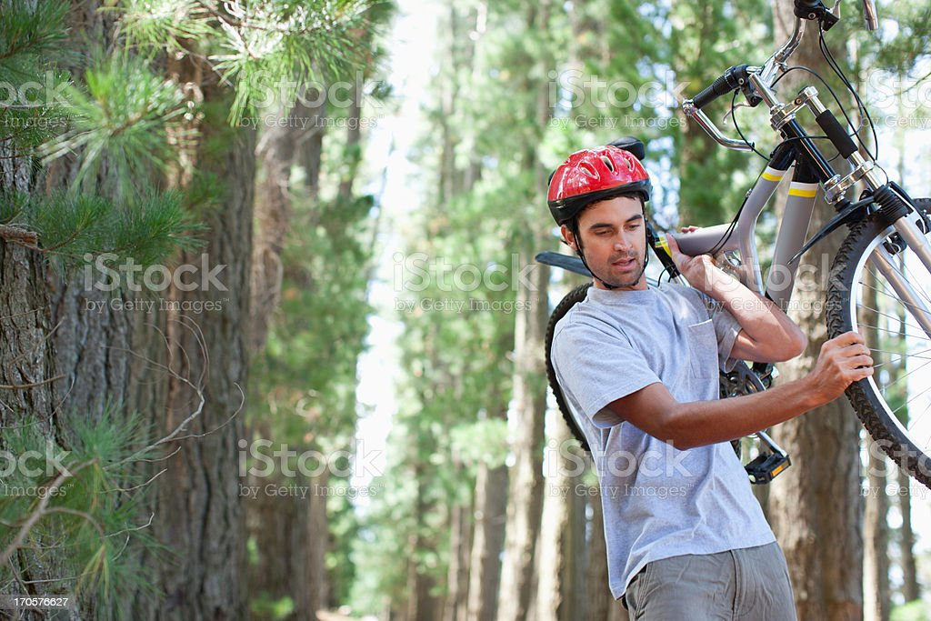 Man carrying bicycle in forest royalty-free stock photo