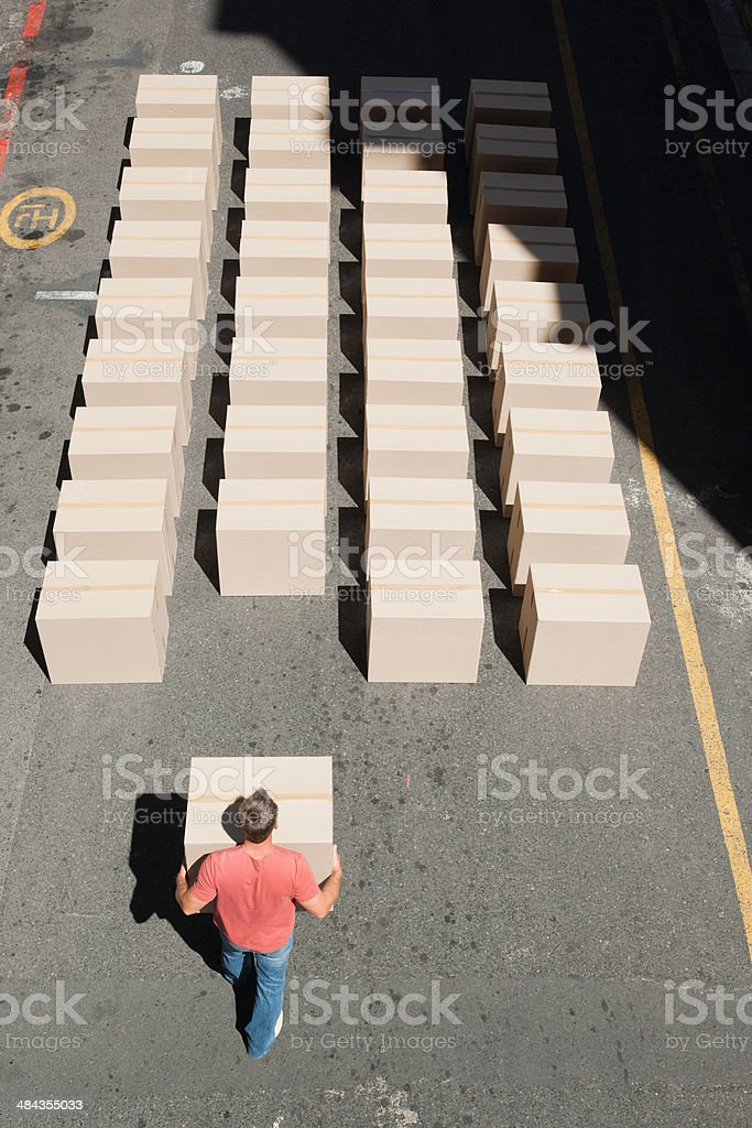 Man carrying box in roadway stock photo
