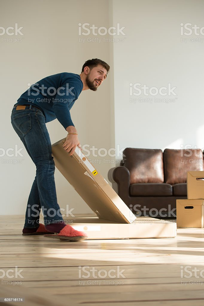 Man carrying boxes at his home stock photo