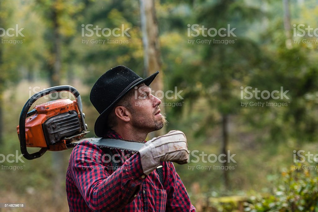 Man carrying chainsaw stock photo