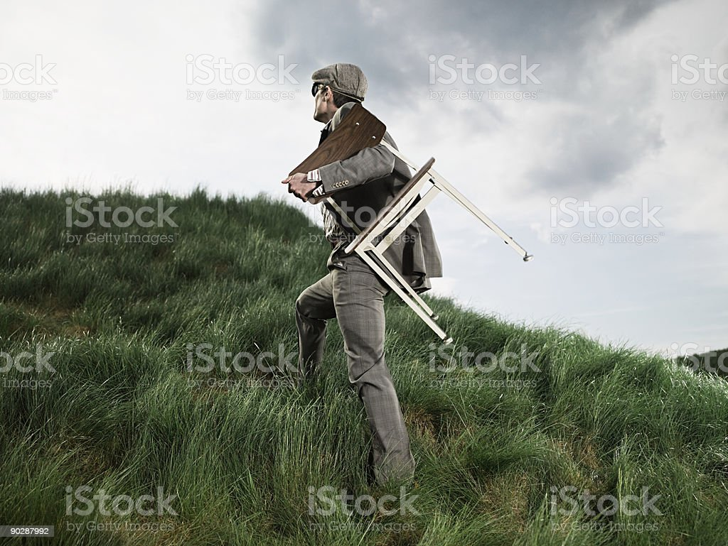 Man carrying chair through field royalty-free stock photo