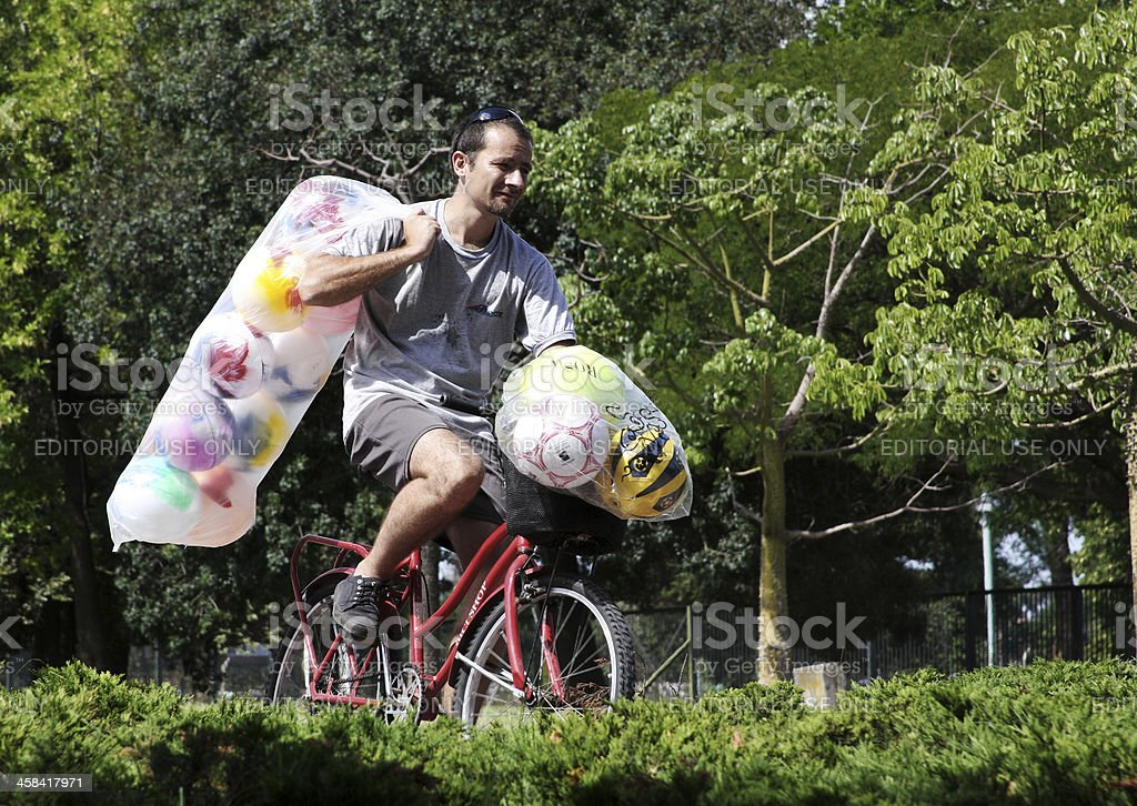 Man Carrying Colorful Balls Rides Through United Nations Park royalty-free stock photo