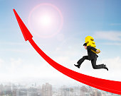 Man carrying Euro sign running on red arrow up graph