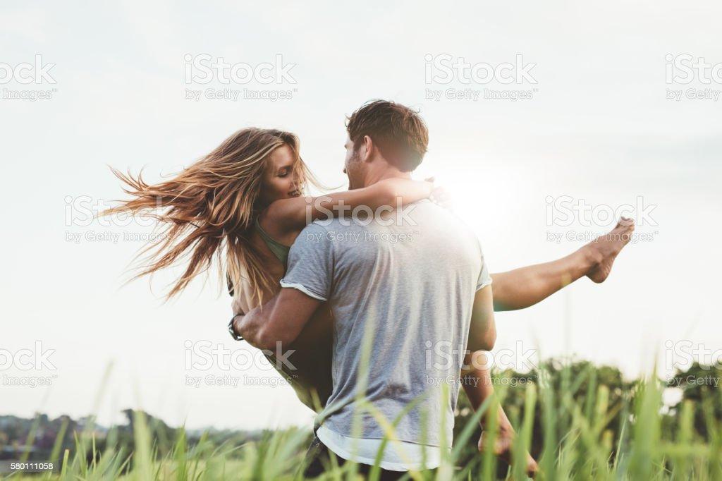 Man carrying girlfriend in  grass field stock photo