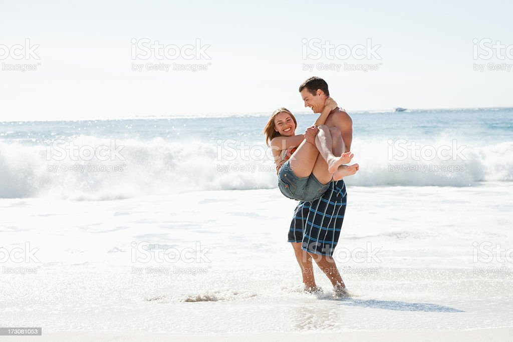 Man carrying girlfriend on beach royalty-free stock photo