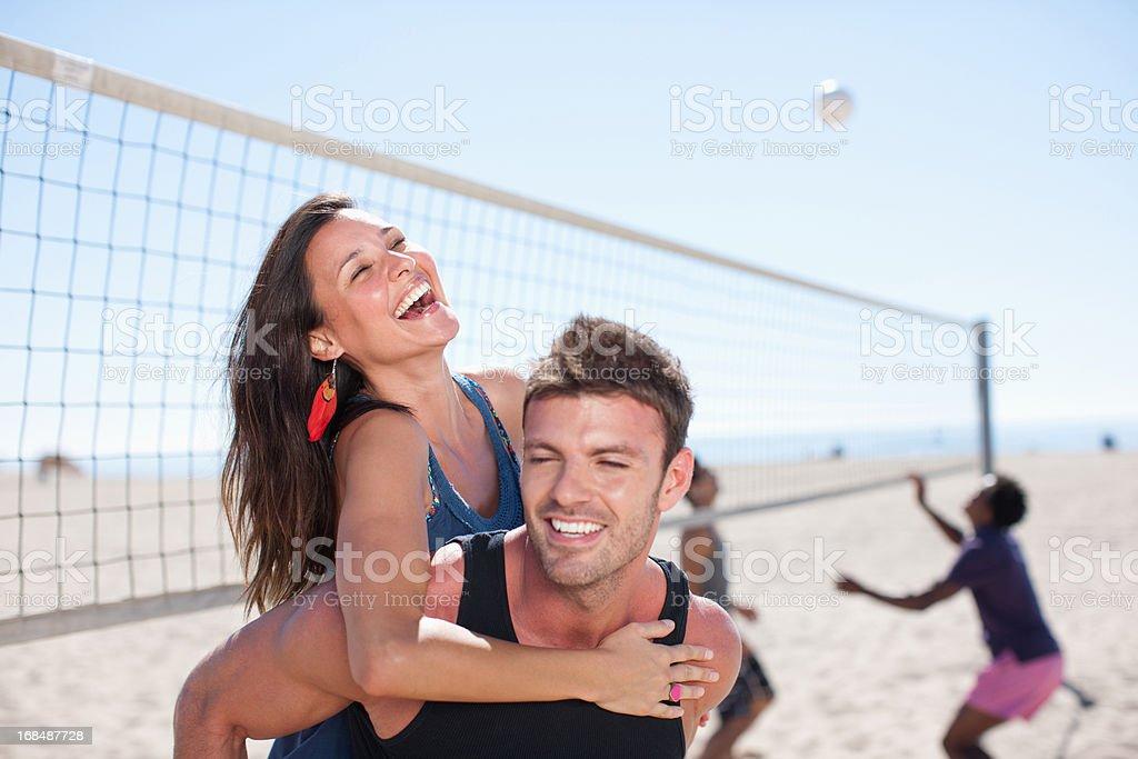 Man carrying girlfriend piggyback on beach royalty-free stock photo