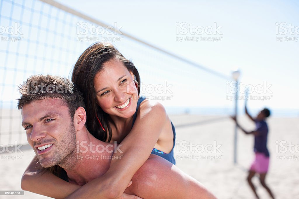 Man carrying girlfriend piggyback on beach royalty-free stock photo