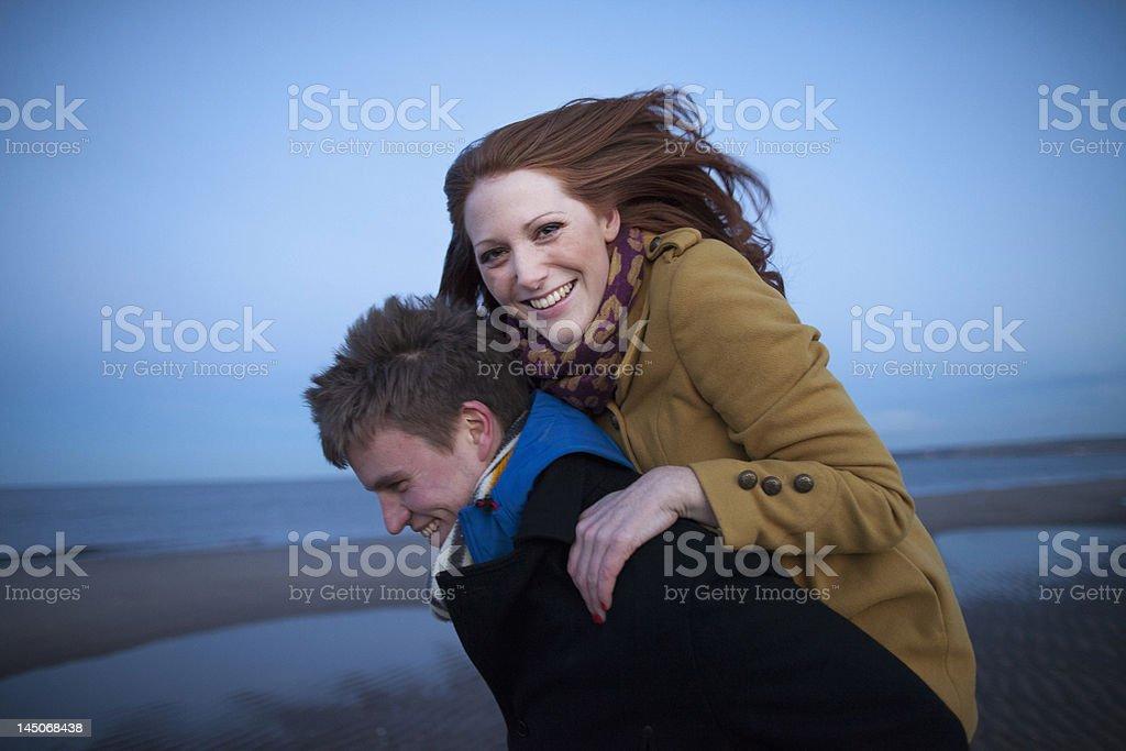 Man carrying girlfriend piggyback stock photo