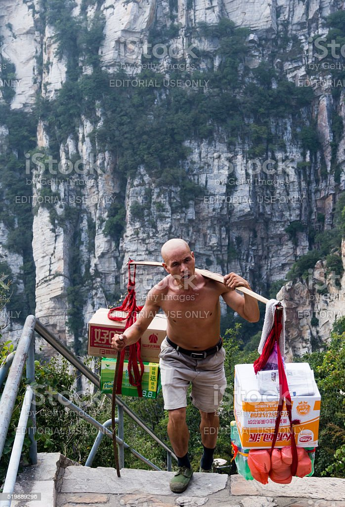Man carrying heavy load up the mountain in China stock photo