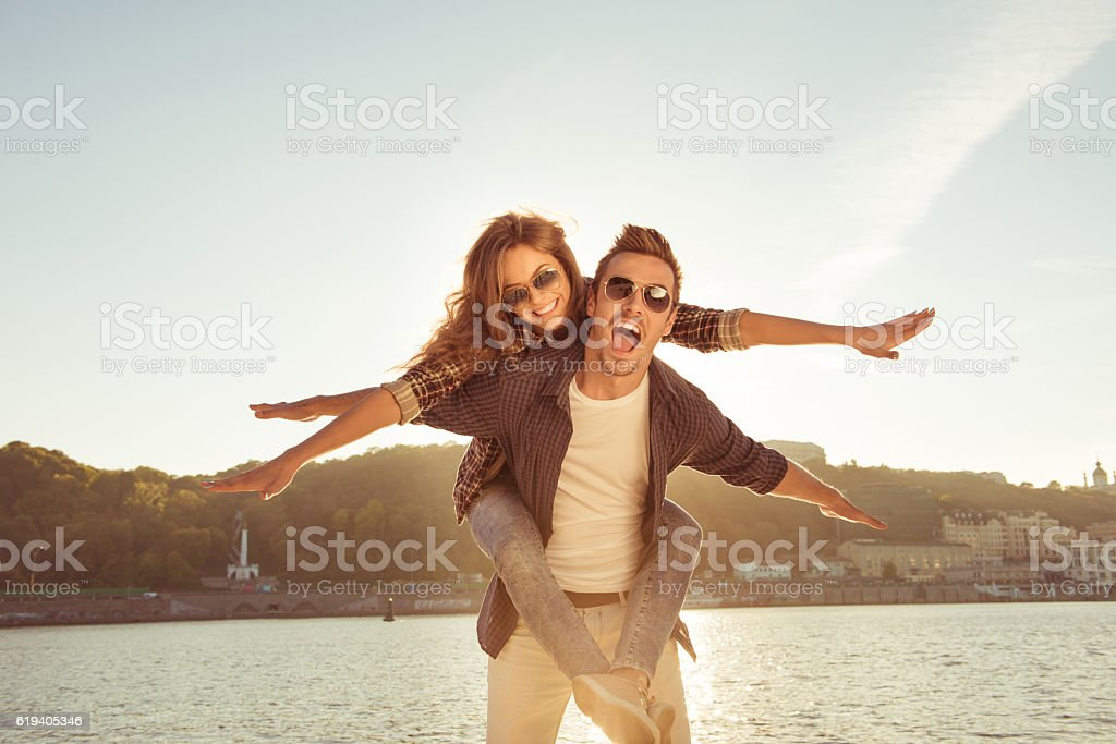 man carrying his gilfriend on the back at the seaside stock photo