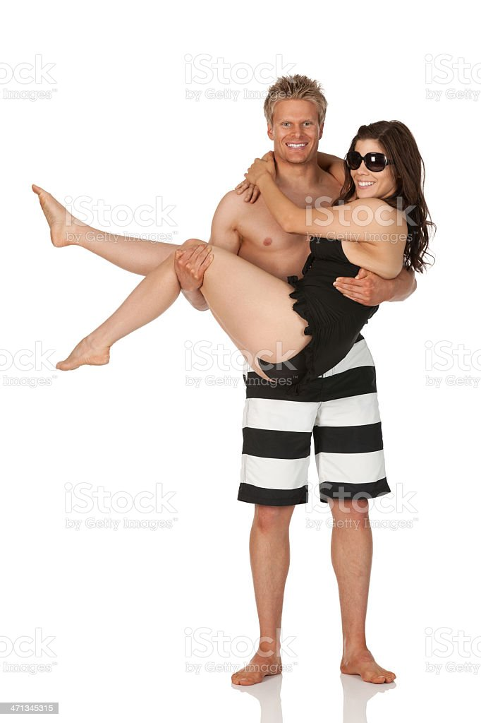 Man carrying his girlfriend and smiling royalty-free stock photo