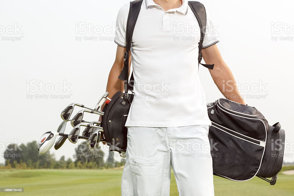 Man carrying his golf bag across course stock photo