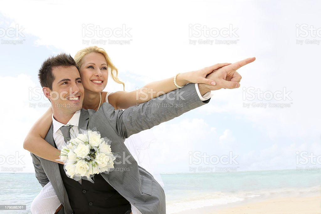 Man carrying his wife on back during wedding royalty-free stock photo
