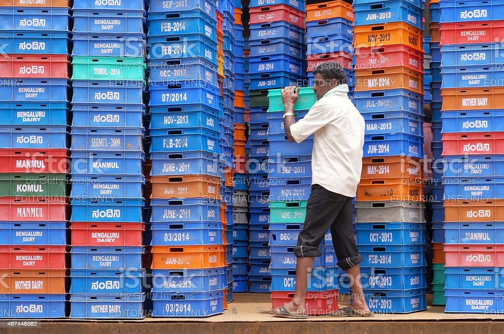 Man carrying milk boxes in a Dairy in Bangalore, India stock photo