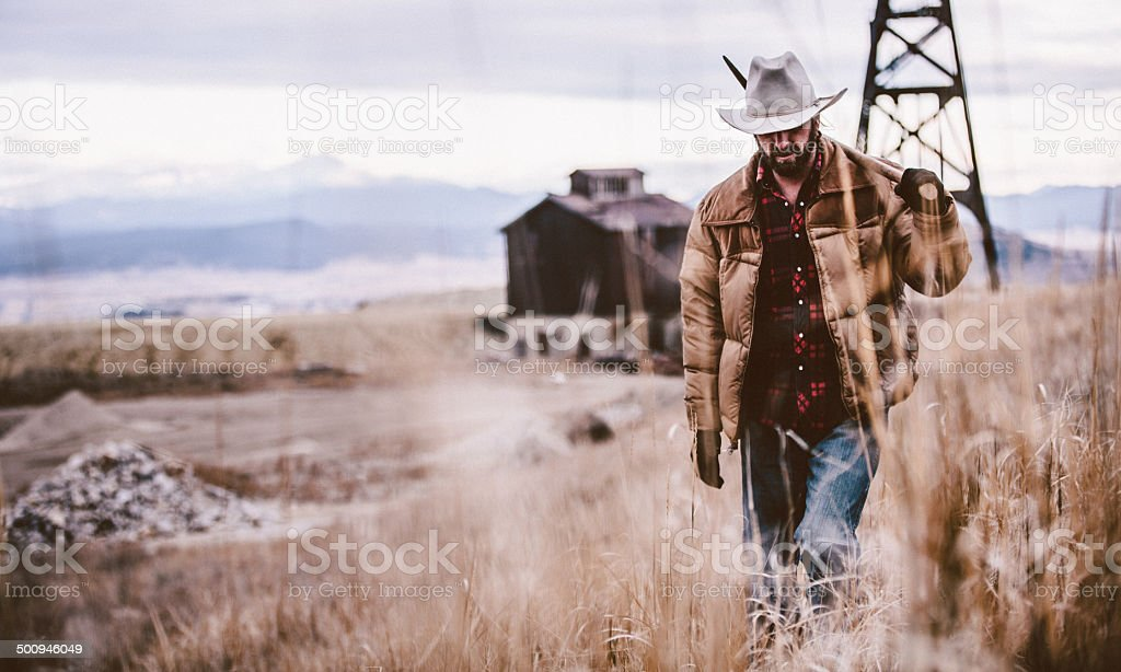 Man carrying pickaxe over shoulder walking through western field stock photo