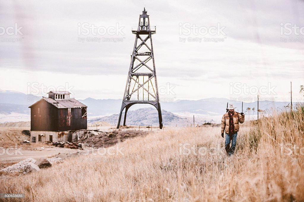 Man carrying pickaxe walking by old oil drill and barn royalty-free stock photo