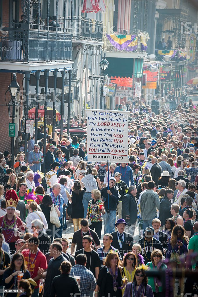 Man carrying scripture passage through Bourbon Street stock photo