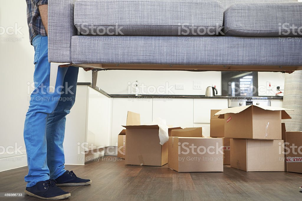 Man Carrying Sofa As He Moves Into New Home royalty-free stock photo