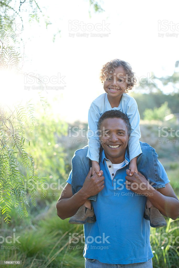 Man carrying son on shoulders stock photo