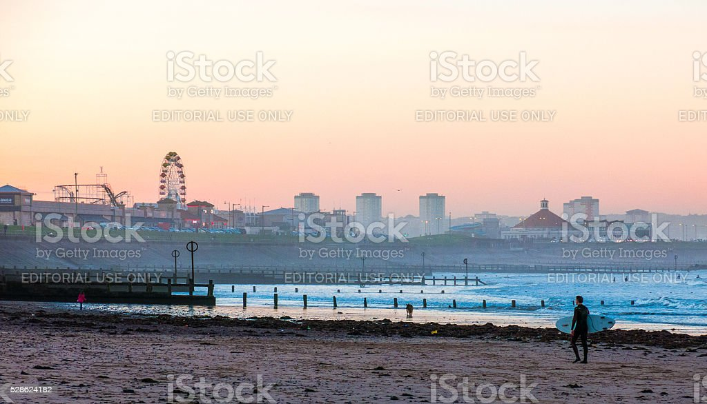 Man Carrying Surfboard on Aberdeen Beach at Sunset stock photo