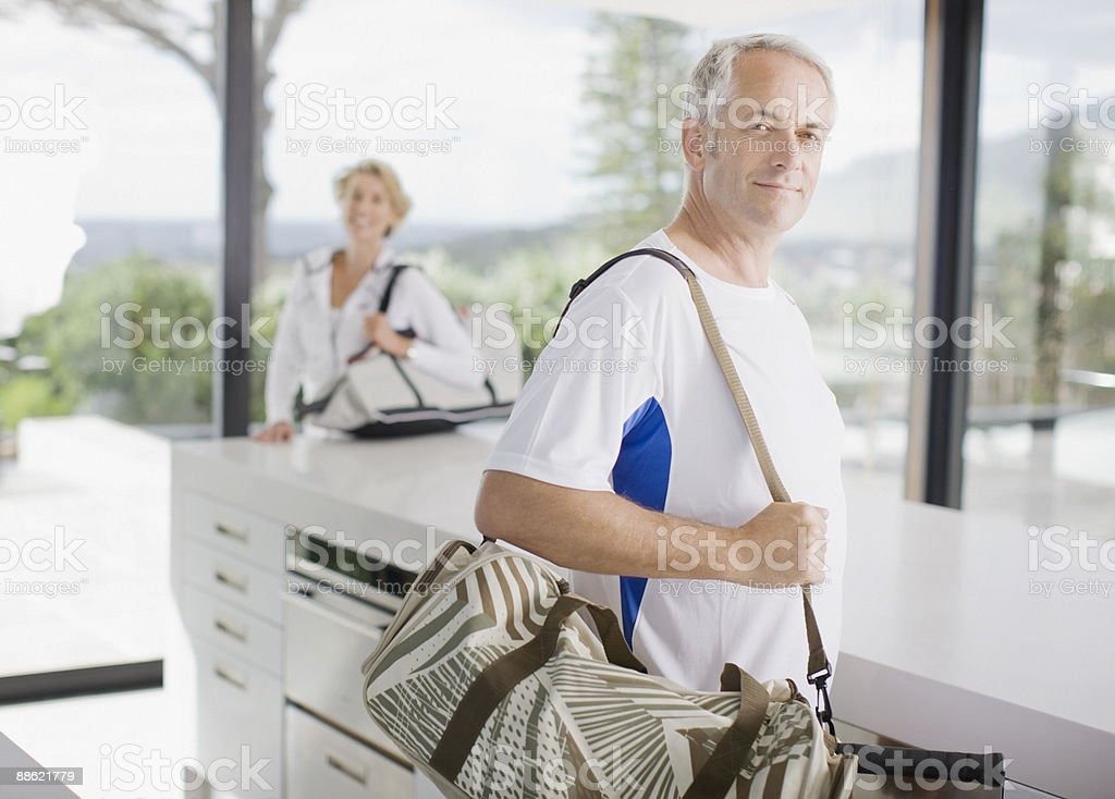 Man carrying tennis racquet in gym bag royalty-free stock photo