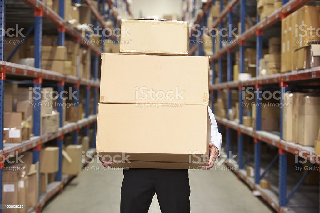 Man carrying three boxes in the warehouse with face covered  stock photo