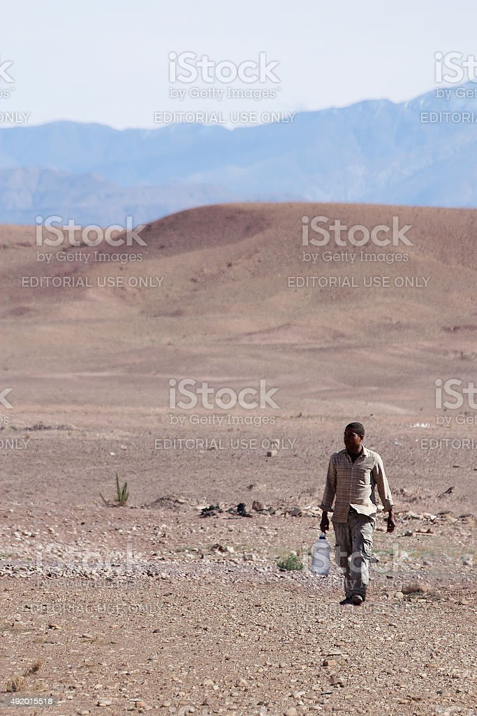 Man carrying water in desert stock photo