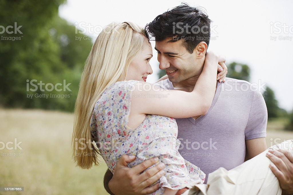 Man carrying woman in rural field royalty-free stock photo