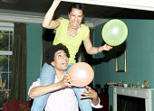 Man carrying woman on shoulders putting up balloon